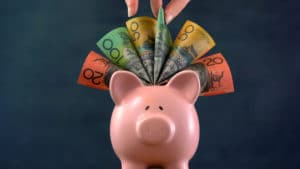 A Melbourne accountant putting money on top of a piggy bank.