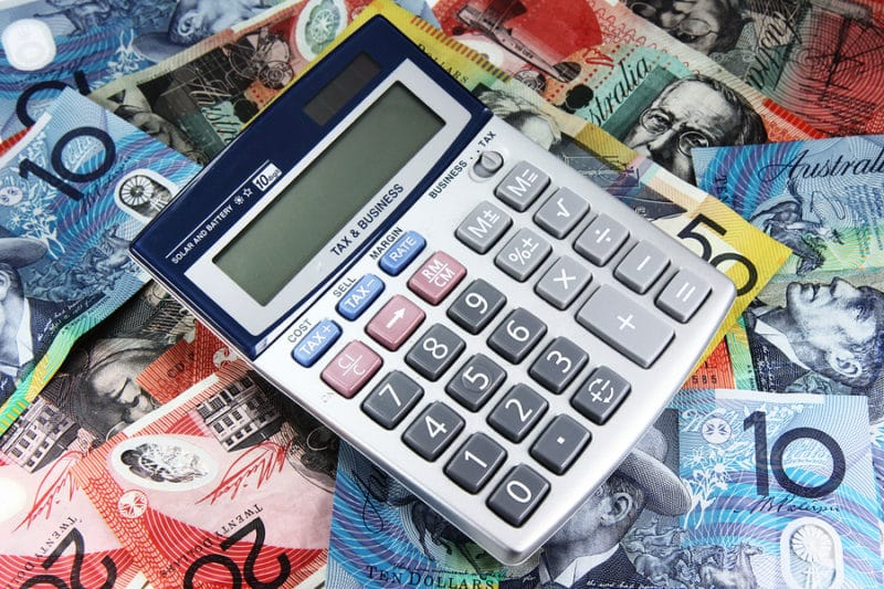 A small business accountant using calculator and money