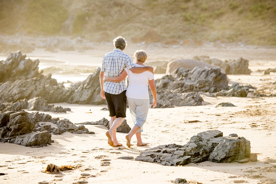 Lovely senior couple on their 60s or 70s retired walking happy and relaxed on beach sea shore in romantic aging together and retirement husband and wife lifestyle concept