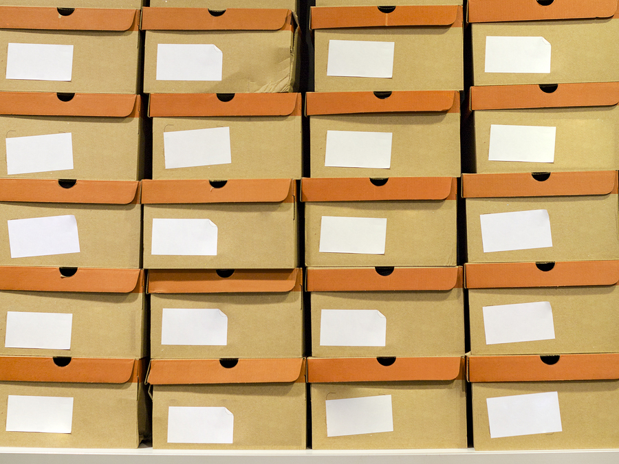 Shoeboxes standing on a shelf in a shoe store. Cardboard boxes on rows of shelves in distribution warehouse. Shoe distribution or delivery warehouse, logistics warehouse dispatch of goods