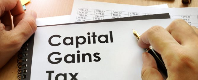 A Melbourne tax accountant holding documents with title capital gains tax.